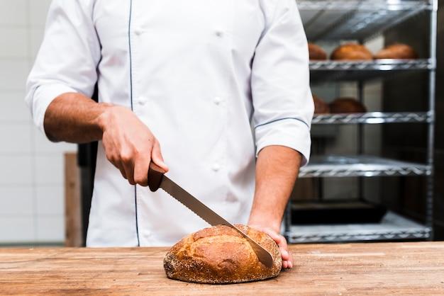 Primer plano de un panadero macho cortando la barra de pan con un cuchillo afilado