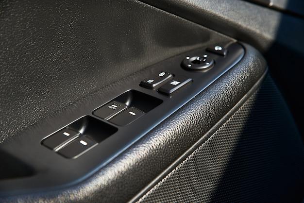 Primer plano de un panel de control de la puerta en un coche nuevo. reposabrazos con panel de control de ventana, botón de bloqueo de puerta y espejo