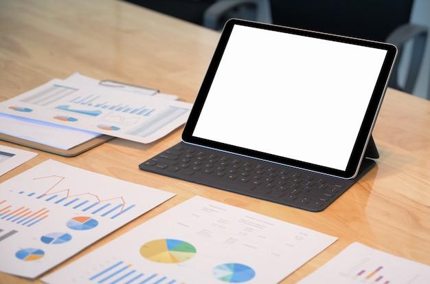 Primer plano de la pantalla en blanco de la tableta moderna mockup con tabla de datos sobre el escritorio.