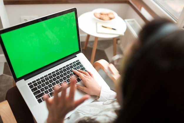 Primer plano de una pantalla de portátil chromakey. una joven trabaja desde la casa en la cocina. video conferencia con colegas