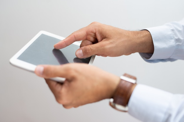 Primer plano de la pantalla táctil del hombre ocupado con el dedo