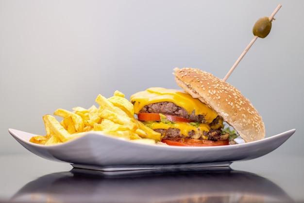 Primer plano de papas fritas y una hamburguesa en un plato bajo las luces contra una pared blanca