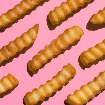 Primer plano de papas fritas sobre fondo rosa