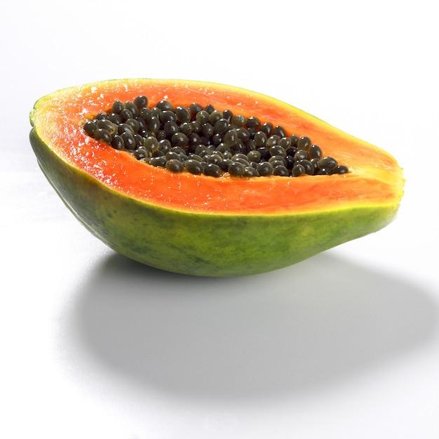Primer plano de una papaya fresca cortada por la mitad aislada sobre una superficie blanca
