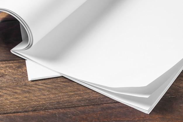 Primer plano de papel en blanco blanco sobre la mesa de madera