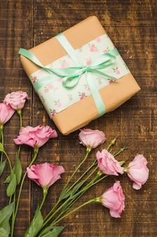 Primer plano de paquete envuelto y rosa flor fresca en la mesa