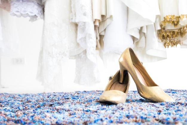 Primer plano de un par de zapatos de novia en sala de montaje con fondo de vestidos de novia