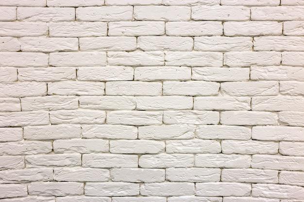 Primer plano de la pared de ladrillo macizo encalado pintado de blanco.