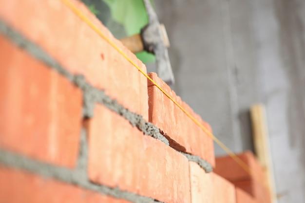 Primer plano de la pared de ladrillo rojo y seda amarilla para medir la distancia entre bloques. equipo de martillo para el trabajo. obra de construcción y concepto de proyecto de renovación.