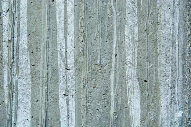 Primer plano de una pared rústica sucia desgastada con manchas de pintura y cemento viejo