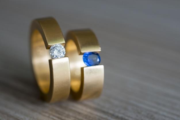 Primer plano de una pareja de anillos de bodas de oro con diamantes y zafiros en la mesa de madera