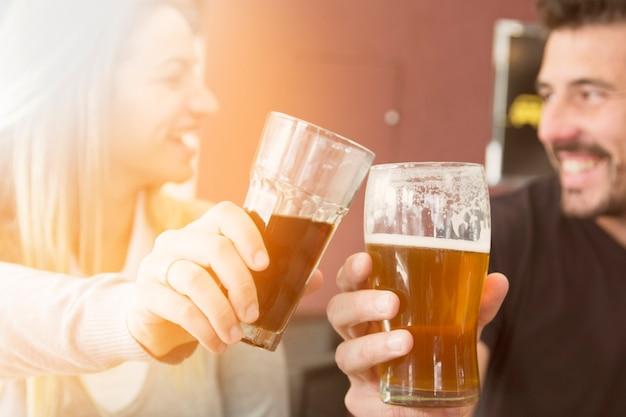 Primer plano de una pareja brindando un vaso de cerveza