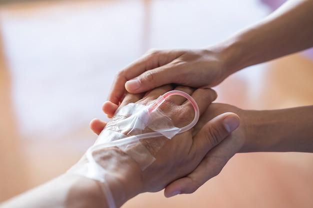 Primer plano de una pareja cogidos de la mano en el hospital