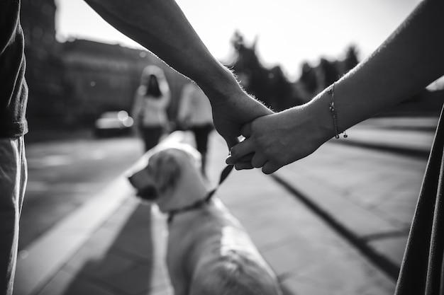 Primer plano de pareja cogiéndose de las manos en blanco y negro