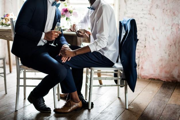Primer plano de la pareja gay tomados de la mano sentados juntos