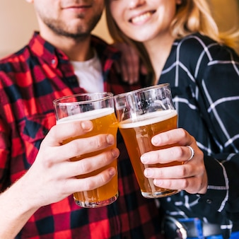 Primer plano de una pareja haciendo clic en los vasos de cerveza