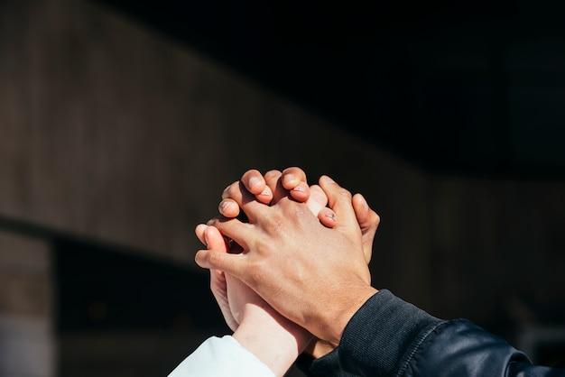 Primer plano de pareja interracial tomados de la mano