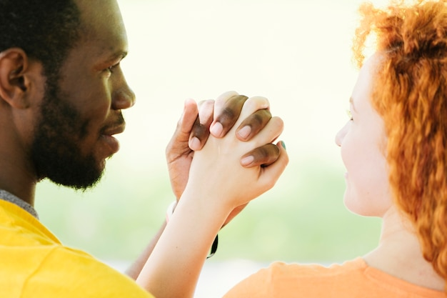 Primer plano de la pareja interracial tomados de la mano