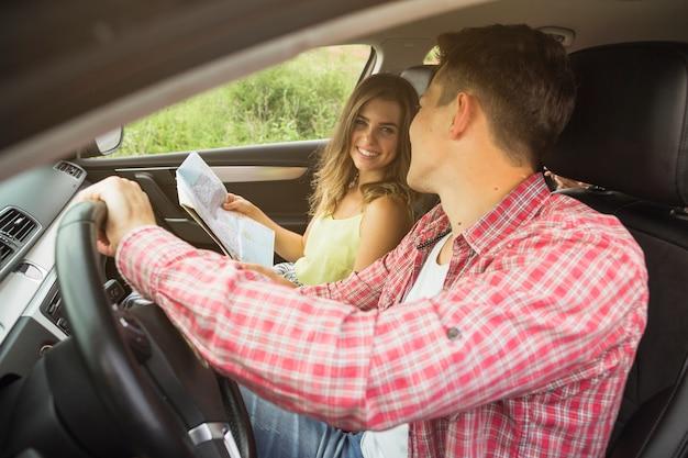 Primer plano de una pareja joven disfrutando de viajar en coche