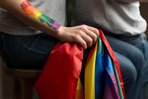 Primer plano de pareja joven lesbiana sosteniendo la bandera lbgt en la mano
