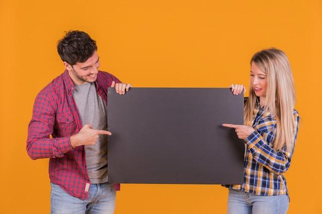 Primer plano de una pareja joven que señala sus dedos en el cartel negro sobre un fondo naranja