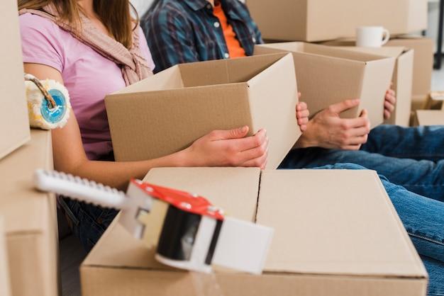Primer plano de pareja joven sosteniendo cajas de cartón en la mano en su nueva casa