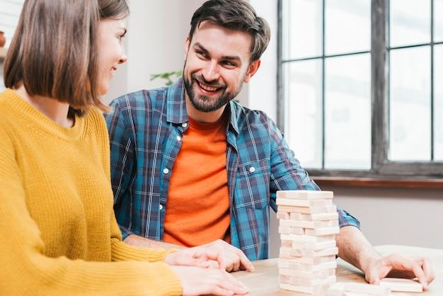 Primer plano de una pareja jugando al juego de apilar bloques en casa