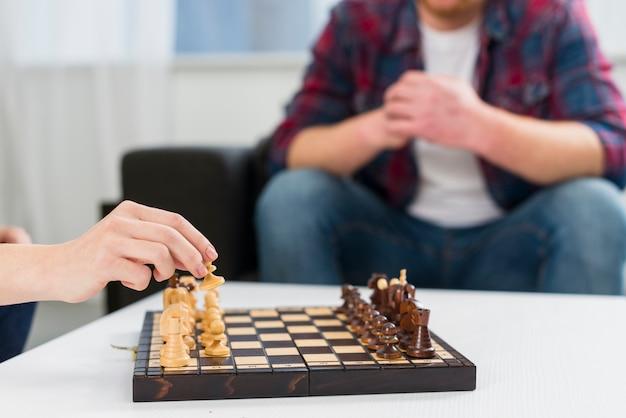 Primer plano de una pareja jugando al tablero de ajedrez de madera en casa