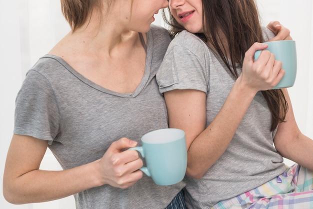 Primer plano de pareja de lesbianas jóvenes bebiendo el café