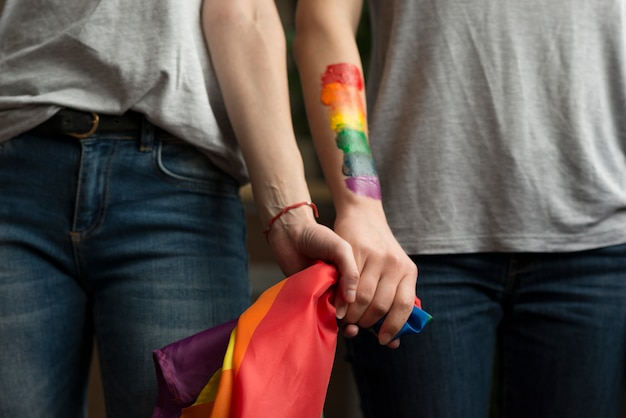 Primer plano de pareja de lesbianas sosteniendo la bandera lbgt en manos