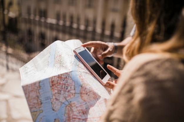 Primer plano de pareja mirando teléfono celular y mapa