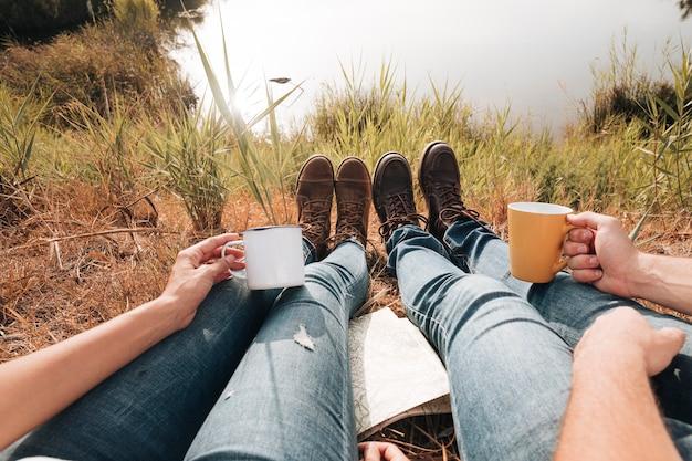 Primer plano de pareja sentada junto al lago