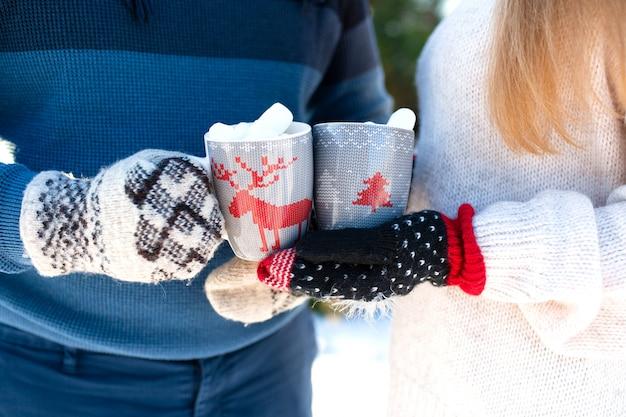 Primer plano de una pareja sosteniendo copas con ciervos con una bebida caliente y malvaviscos en sus manos con guantes de invierno cálido