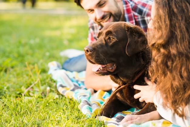 Primer plano de una pareja con su perro en el parque