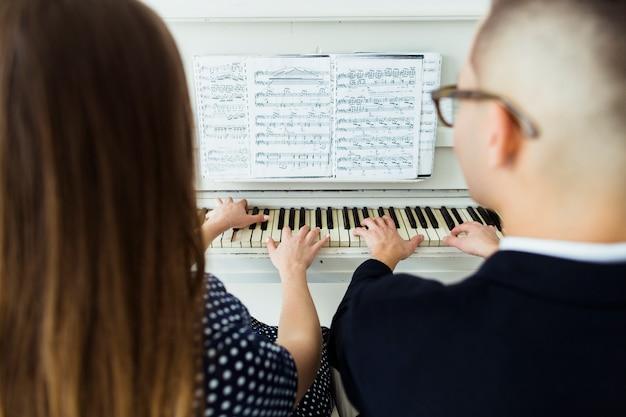 Primer plano de pareja tocando el piano con la hoja musical