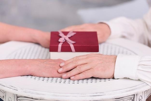 Primer plano de una pareja tomados de la mano cerca de caja de regalo en la mesa