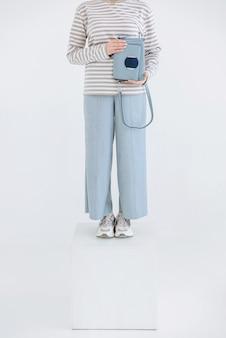 Primer plano de la parte del cuerpo femenino de la pierna de pie en el cubo en la escena blanca sosteniendo el bolso