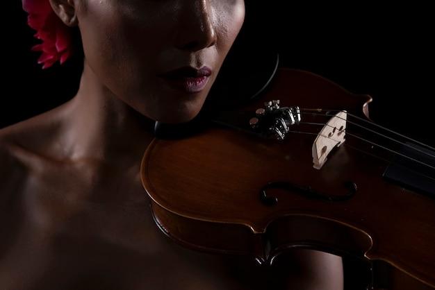 Primer plano de la parte delantera del violín se puso al lado de la cara de la mujer