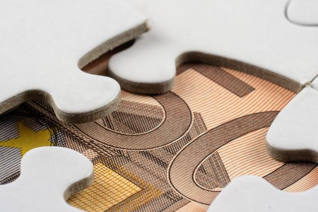 Primer plano de una parte del dinero visto debajo de una pieza extraída de un rompecabezas