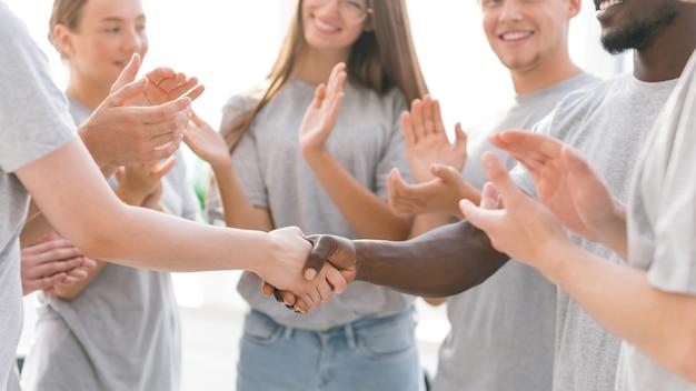 Primer plano de los participantes del foro de jóvenes aplaudiendo a sus líderes