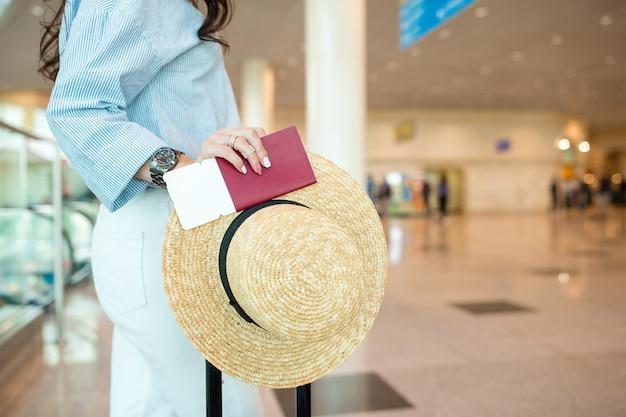 Primer plano de pasaportes y tarjeta de embarque en manos femeninas en el aeropuerto