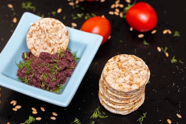 Primer plano de pasta de oliva en un recipiente sobre la mesa con galletas y tomates bajo las luces