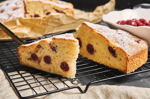 Primer plano de un pastel de cerezas con azúcar en polvo e ingredientes en el lado negro