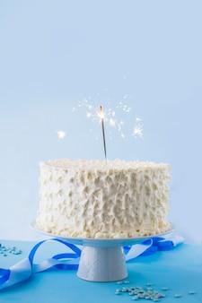 Primer plano de pastel de cumpleaños blanco con bengala ardiente