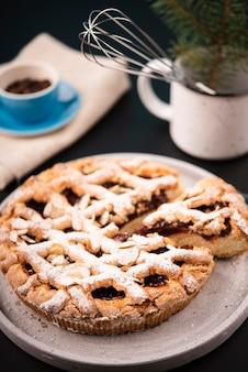Primer plano de pastel en rodajas con granos de café desenfocados y pino