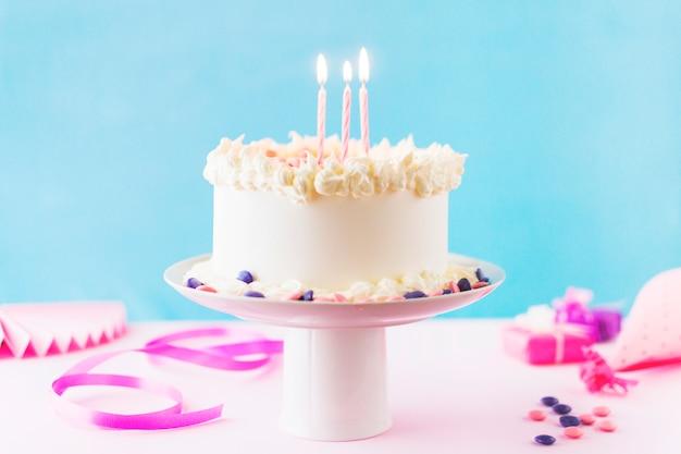 Primer plano de pastel con velas encendidas sobre fondo rosa