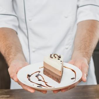 Primer plano de pastelero presentando postre