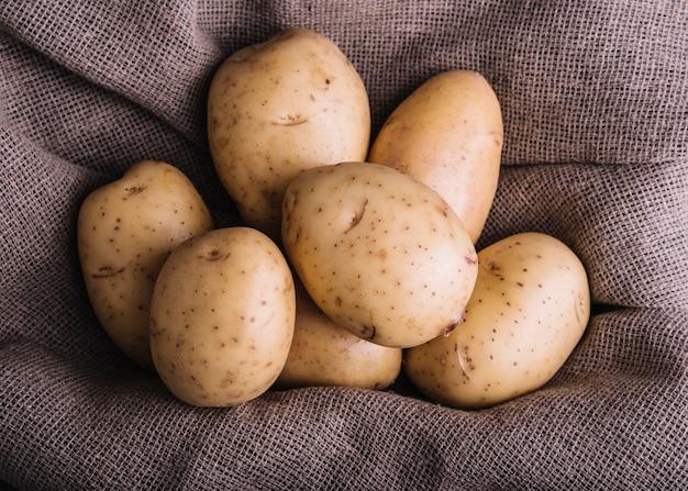 Primer plano de patatas crudas en textil saco