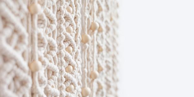 Primer plano del patrón de textura de macramé hecho a mano con cuentas de madera. tejido moderno ecológico. concepto de decoración natural en el interior. enfoque suave. copie el espacio. bandera