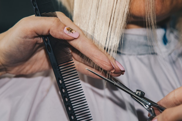 Primer plano de un peluquero corta el cabello blanco mojado de un cliente en un salón. peluquería corta a una mujer. vista lateral de una mano cortando el pelo con unas tijeras.